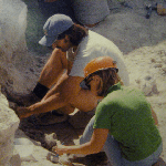 Photo of two people digging for fossils