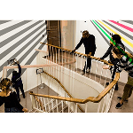 People leaning on a wooden handrail looking at a striped design on a wall